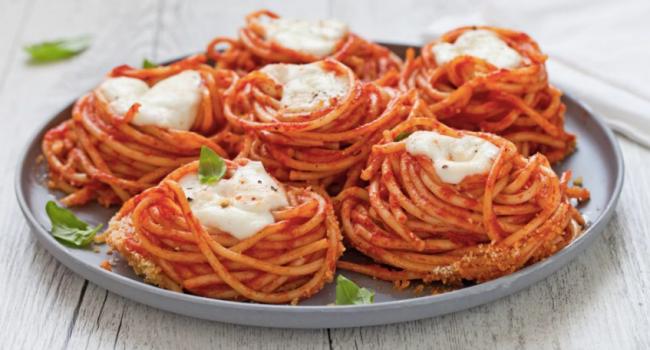 I nidi di spaghetti al forno con mozzarella e salsa di pomodoro alla vaniglia